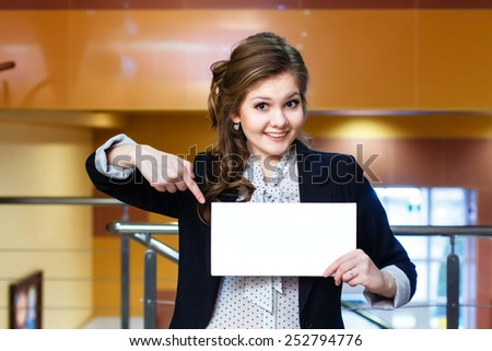 Smiling young beautiful girl shows on blank white card - stock photo