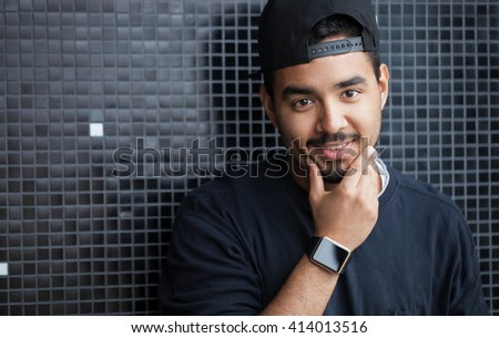 Smiling young black boy wearing trendy smart watches. Modern gadget that lets you always stay connected to internet,social media from everywhere - stock photo