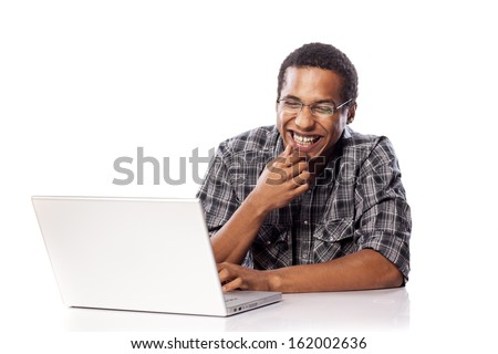 smiling young black man chatting on his laptop - stock photo