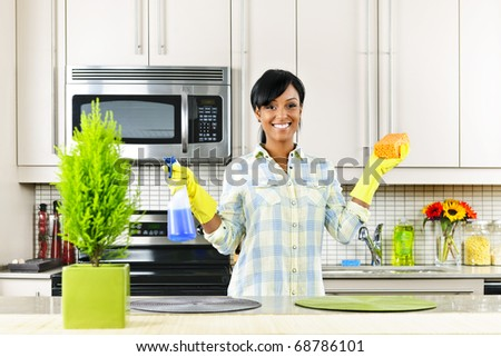 Smiling young black woman with sponge and rubber gloves cleaning kitchen