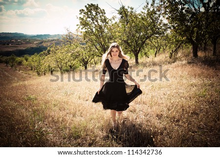 smiling young blond woman in elegant black dress running across field - stock photo