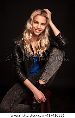 smiling young blond woman in leather jacket resting her head on hand , looking at the camera while sitting