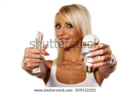 smiling young blonde holding led bulb and money