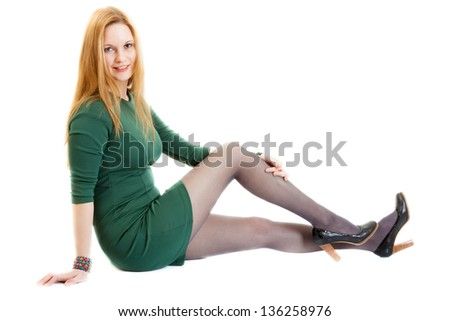 smiling young blonde woman wearing a green dress, black panti-tights and black sandals - stock photo