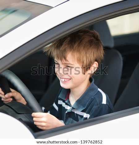 Smiling young boy driving a car in a close up portrait - stock photo