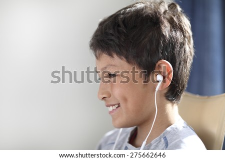 Smiling young boy in profile with earphones - shallow depth of field - stock photo