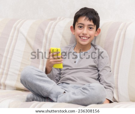 smiling young boy with smart phone - stock photo
