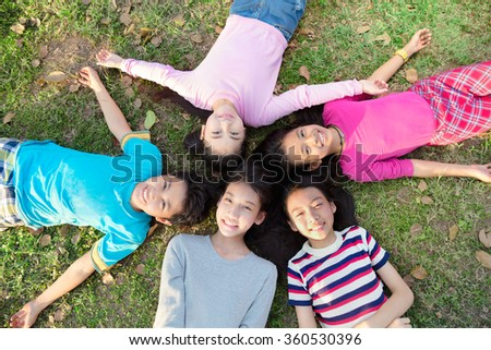 Smiling young boys and girls lying on green grass - stock photo