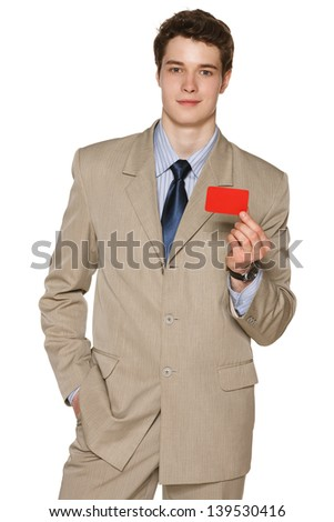 Smiling young business man holding blank credit card, against white background - stock photo