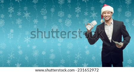 smiling young business man in santa hat holding money over winter snowflakes background - stock photo