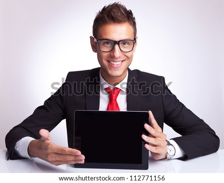 smiling young business man presenting a touchscreen  pad tablet at his desk - stock photo
