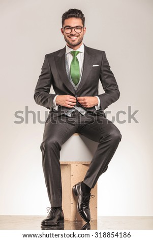 Smiling young business man sitting on wood boxes while closing his jacket.