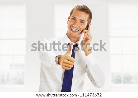 smiling young business man talking on the phone and making ok - stock photo
