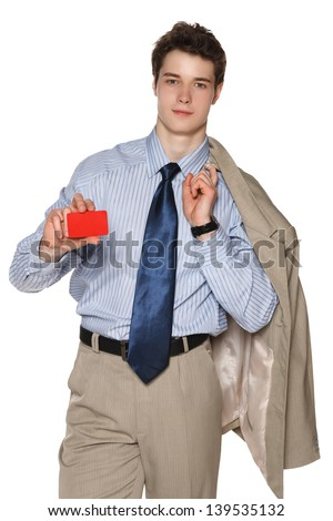 Smiling young business man with suit over shoulder holding blank credit card, against white background - stock photo
