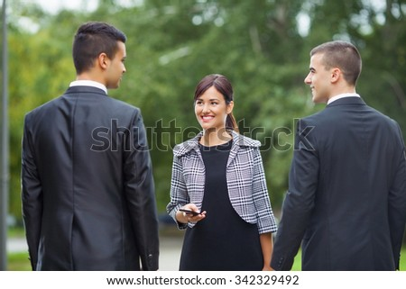 Smiling young business people meeting on the street - stock photo