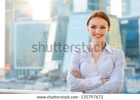 Smiling young business woman on the modern city downtown background - stock photo