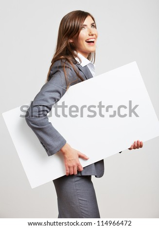 Smiling young business woman showing blank sign board, over studio  background isolated - stock photo