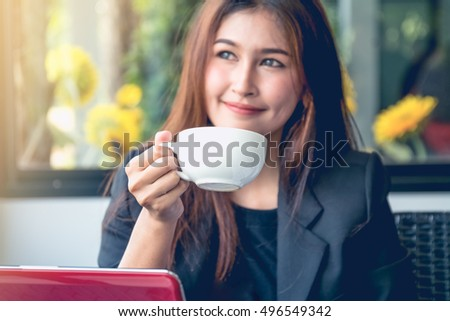 Smiling young business woman sitting at the office desk with a cup of coffee and a laptop.