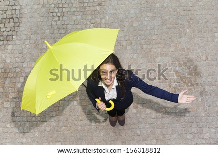 Smiling young business woman with yellow umbrella checking if it's raining  - stock photo