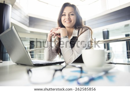 Smiling young business woman working for a laptop in a modern office. - stock photo