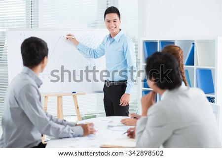 Smiling young businessman conducting presentation in front of his colleagues - stock photo