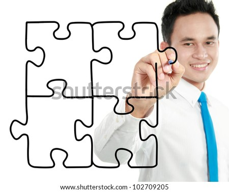 smiling young businessman drawing puzzle concept on white background