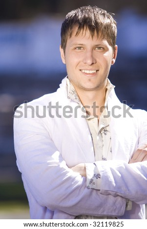 smiling young businessman in the street - stock photo