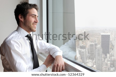 Smiling young businessman looking out of a window - stock photo