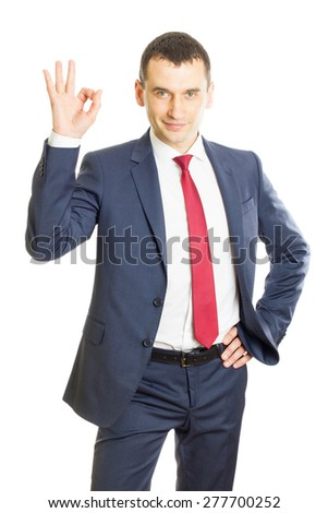 Smiling young businessman making ok gesture - stock photo