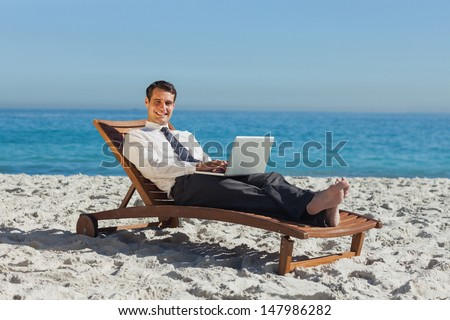 Smiling young businessman on the beach lying on a deck chair with his laptop - stock photo