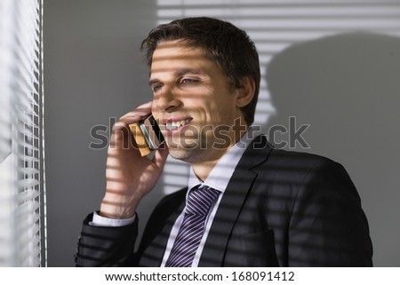Smiling young businessman peeking through blinds while on call in the office - stock photo