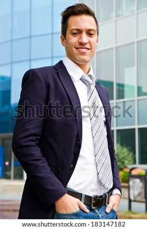 Smiling young businessman standing outside a building