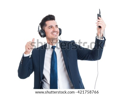 Smiling young businessman taking a selfie while listening music and thumb up isolated on white - stock photo