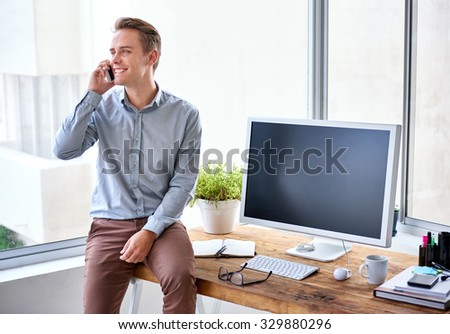 Smiling young businessman talking on his phone while sitting casually on the edge of his wooden desk in a bright work space - stock photo