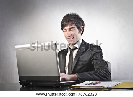 Smiling young businessman using a laptop