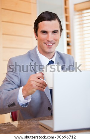 Smiling young businessman with laptop and coffee - stock photo
