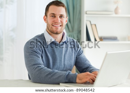 Smiling young businessman with laptop in his home office
