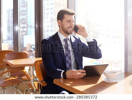 Smiling young businessman with touchpad and coffee, mobile - stock photo