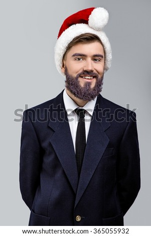 Smiling young businessman, with violet beard, wearing in dark blue suit, santa heat and tie, posing on white background, in studio, waist up - stock photo