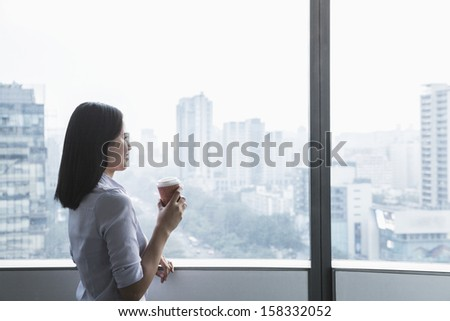 Smiling young businesswoman holding a coffee cup and looking out the window  - stock photo