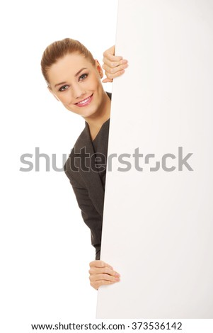 Smiling young businesswoman holding blank banner - stock photo