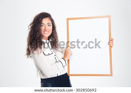 Smiling young businesswoman holding blank board isolated on a white background. Looking at camera - stock photo