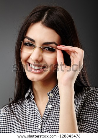 Smiling young businesswoman in closeup pose on gray background - stock photo