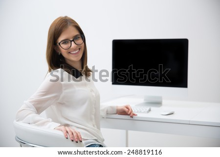 Smiling young businesswoman in glasses at office