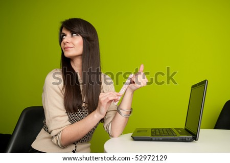 Smiling young businesswoman or office worker filing fingernails at work - stock photo