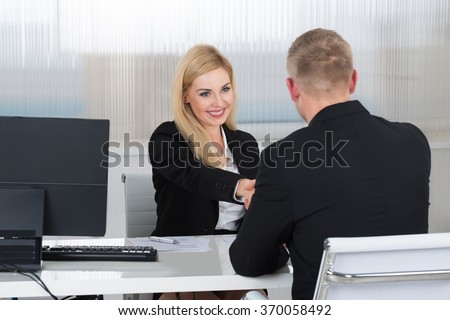Smiling young businesswoman shaking hands with male candidate at desk in office