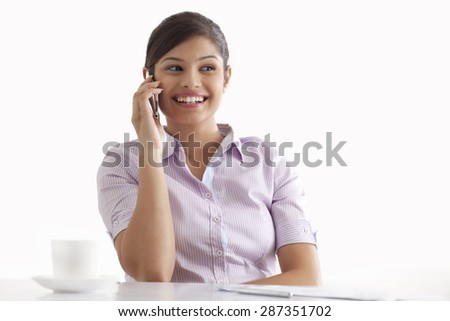 Smiling young businesswoman using cell phone at her desk