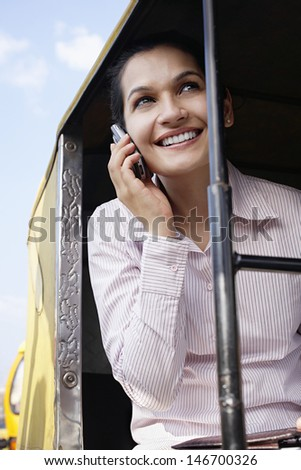 Smiling young businesswoman using cell phone in tuk-tuk taxi - stock photo