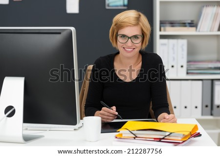 Smiling young businesswoman working in an office sitting at her desk attending to paperwork - stock photo