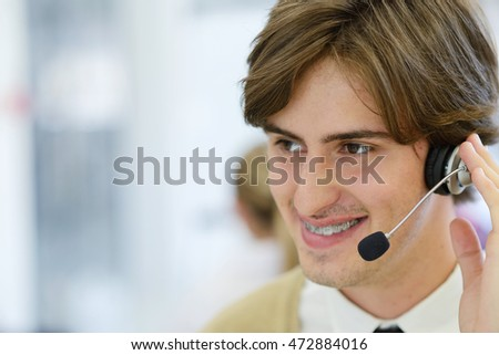 Smiling young call center executive at startup office